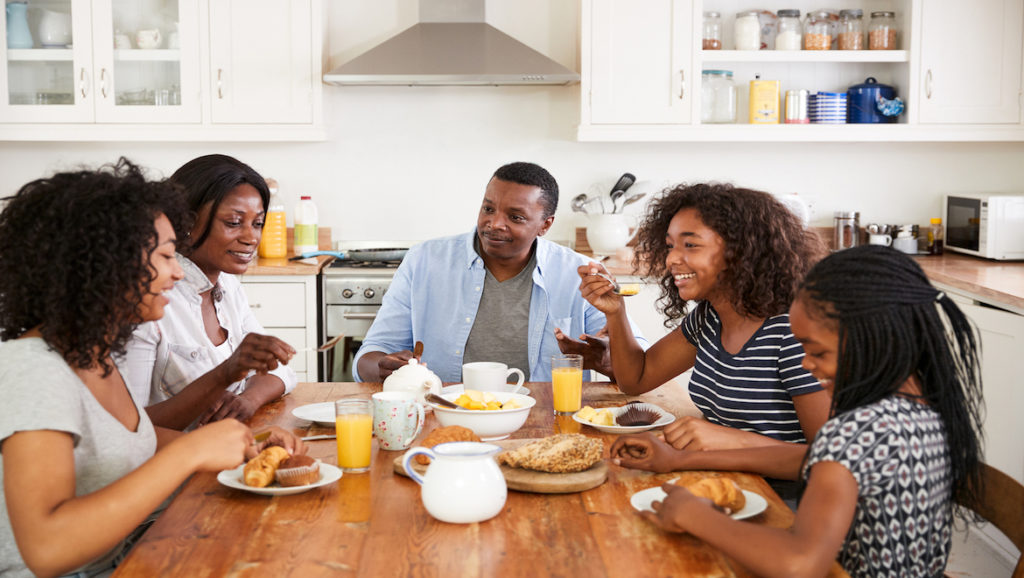 Family of five sitting at the table in the kitchen smiling and conversing over breakfast