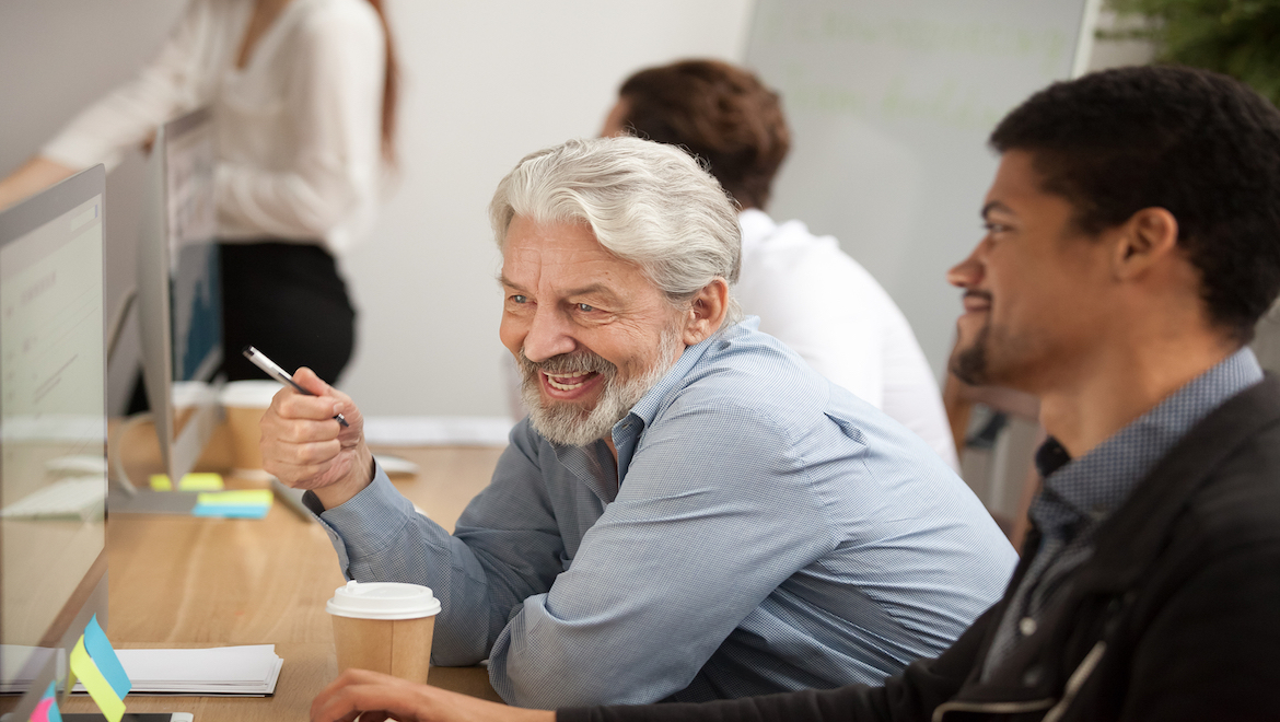 Smiling grey haired man talking to coworker