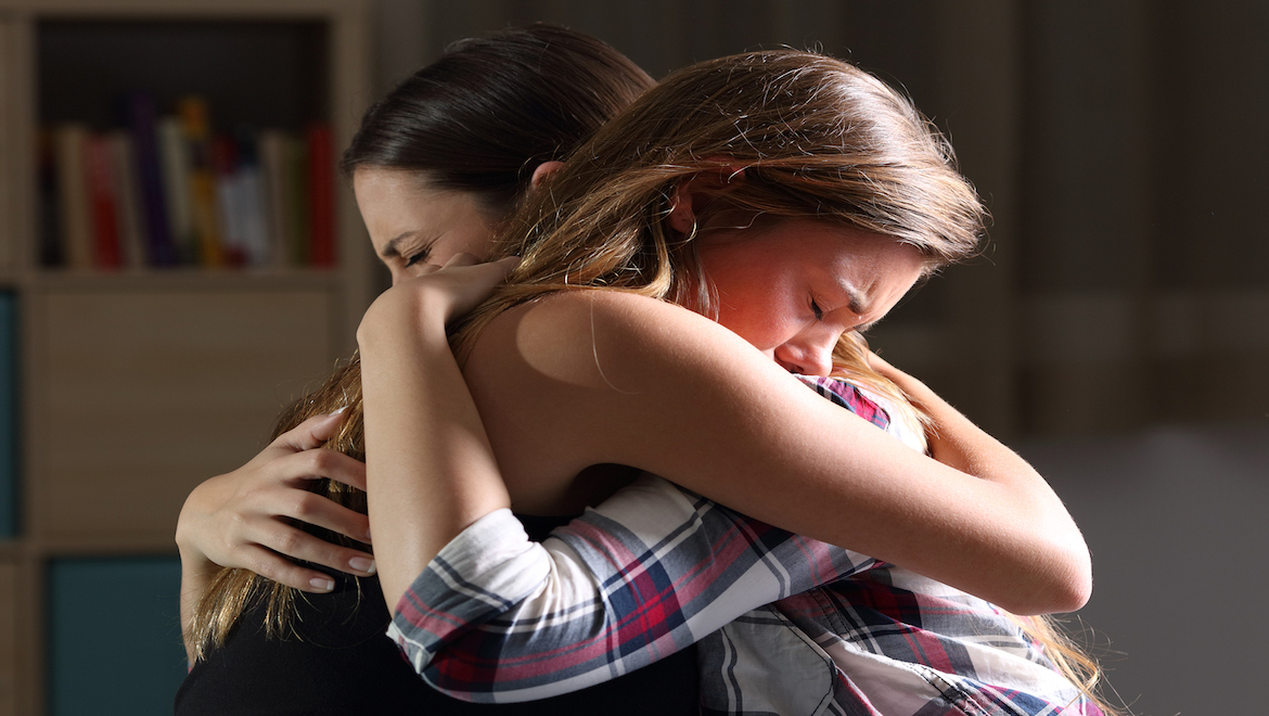 girls hugging and crying after forgiveness