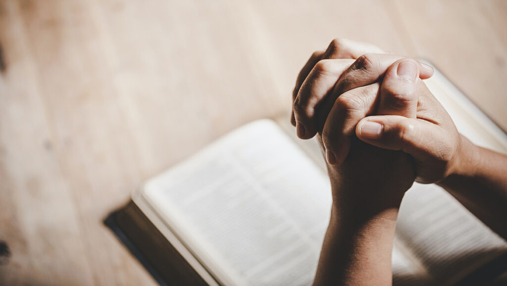 Hands clasped over Bible to remedy feeling fearful