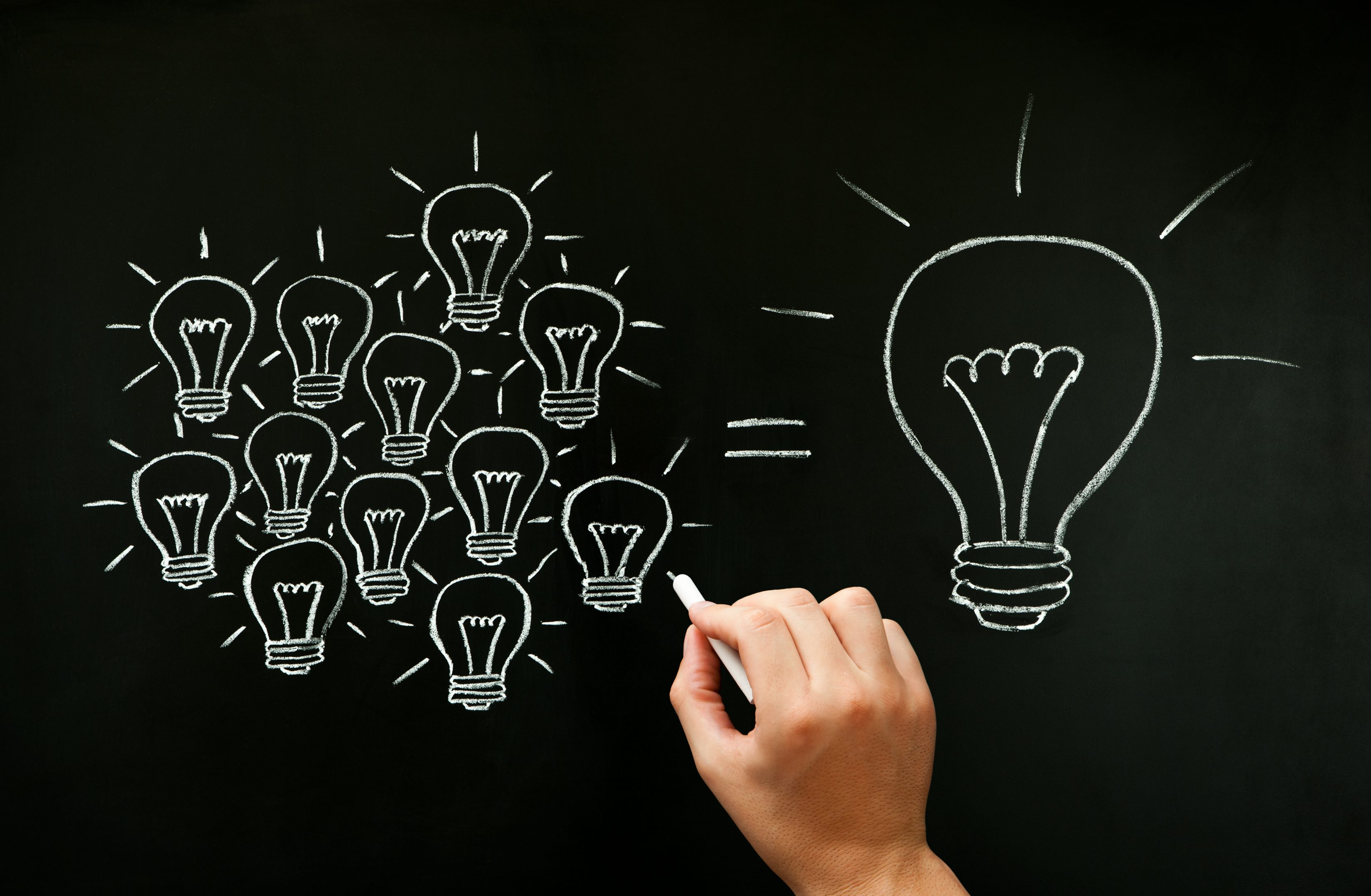 Hand drawing with chalk on blackboard light bulbs concept illustrating how a team is working together creating a great idea. Many small ideas add up to a big one.